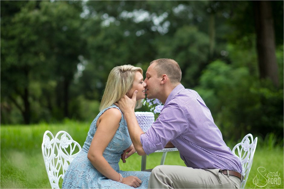 Couple kissing during unique engagement session with cupcake theme