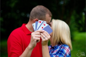 Engagement session of couple kissing with playing cards