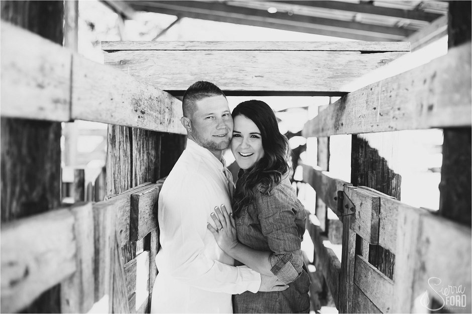Couple poses and smiles at camera inside barn stock walls
