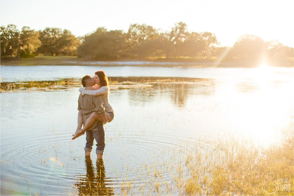 Beautiful couple kissing standing in lake at sunset