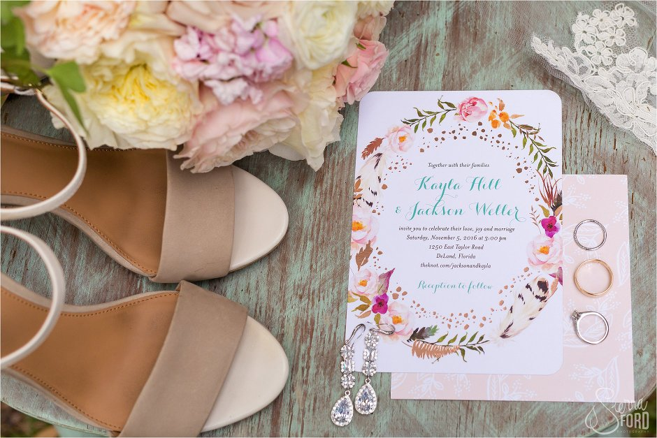 Wedding details inclduing rings, invitations, and flowers