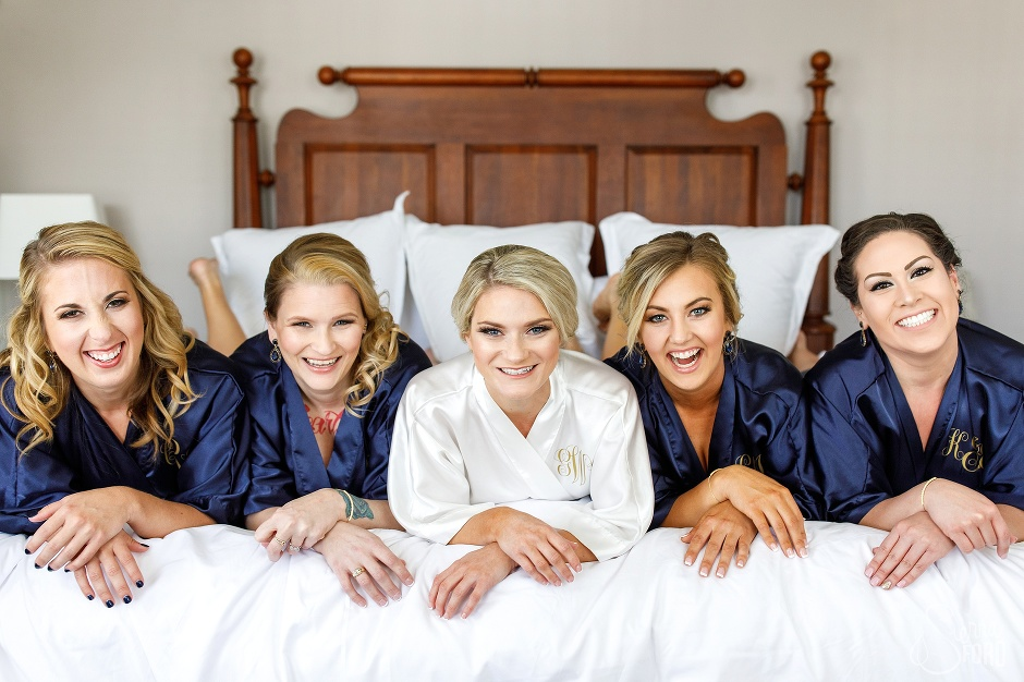 bride and bridesmaids on bed in robes