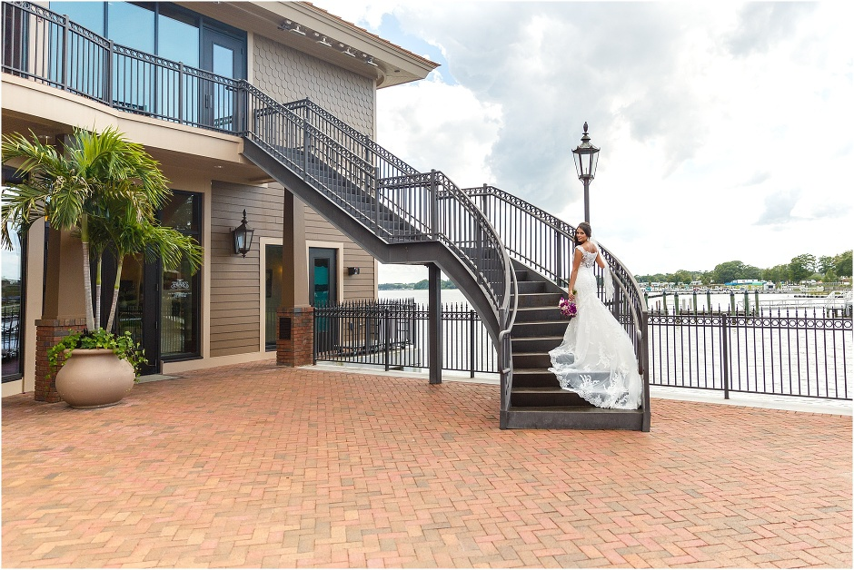 Bride standing on sweeping staircase on scenic pier