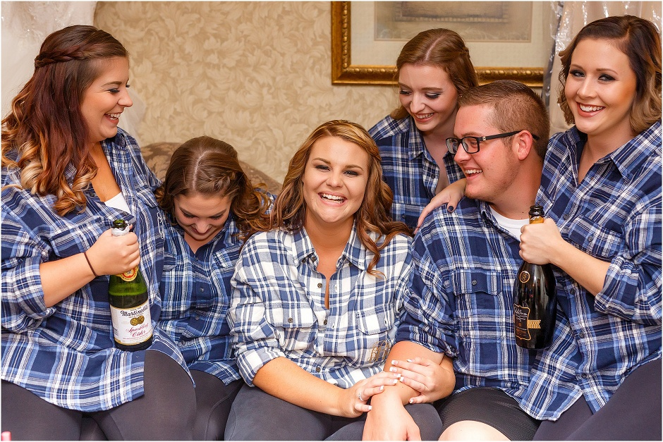 Bride surrounded by her smiling bridesmaids in their matching flannels while they get her ready
