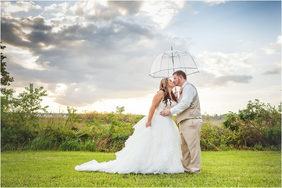 Bride and groom kiss under an umbrella with the lake at Lake Receptions behind them