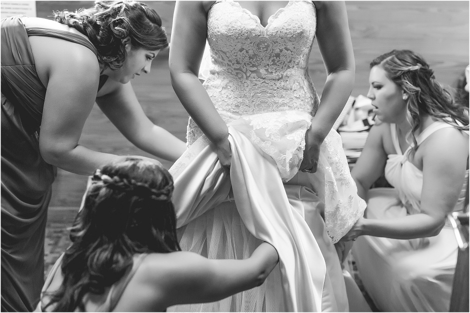 black and white photo of the bridesmaids helping the bride get her dress on