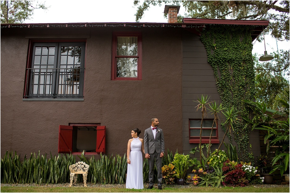 Bride & Groom holding hands in front of big brown house at The Acre Orlando