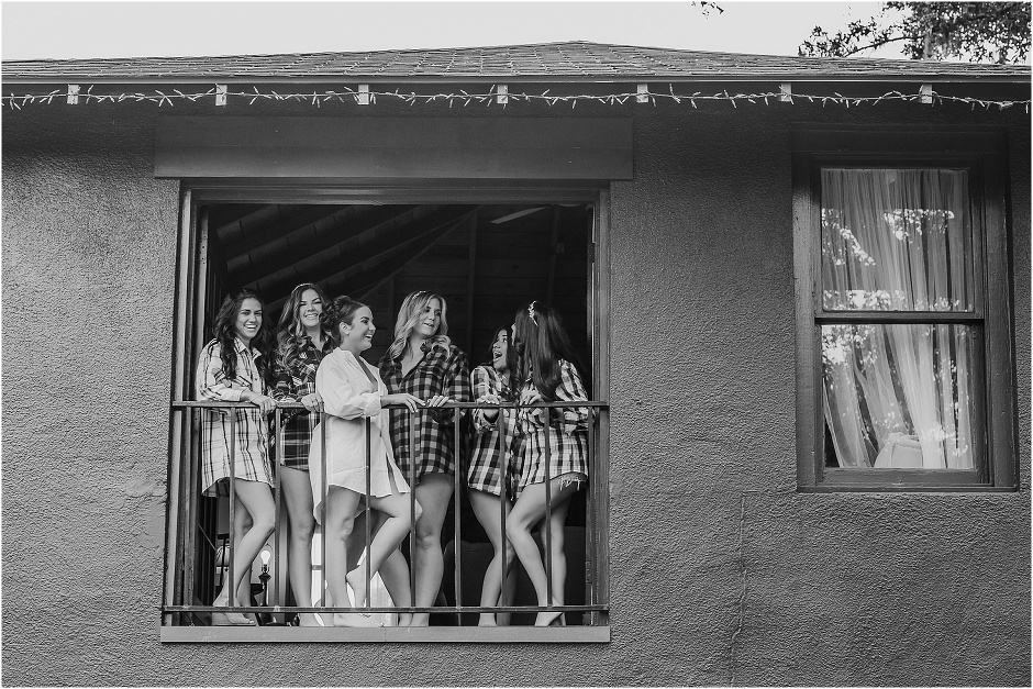 bride and her bridesmaids giggling in the window in matching flannels