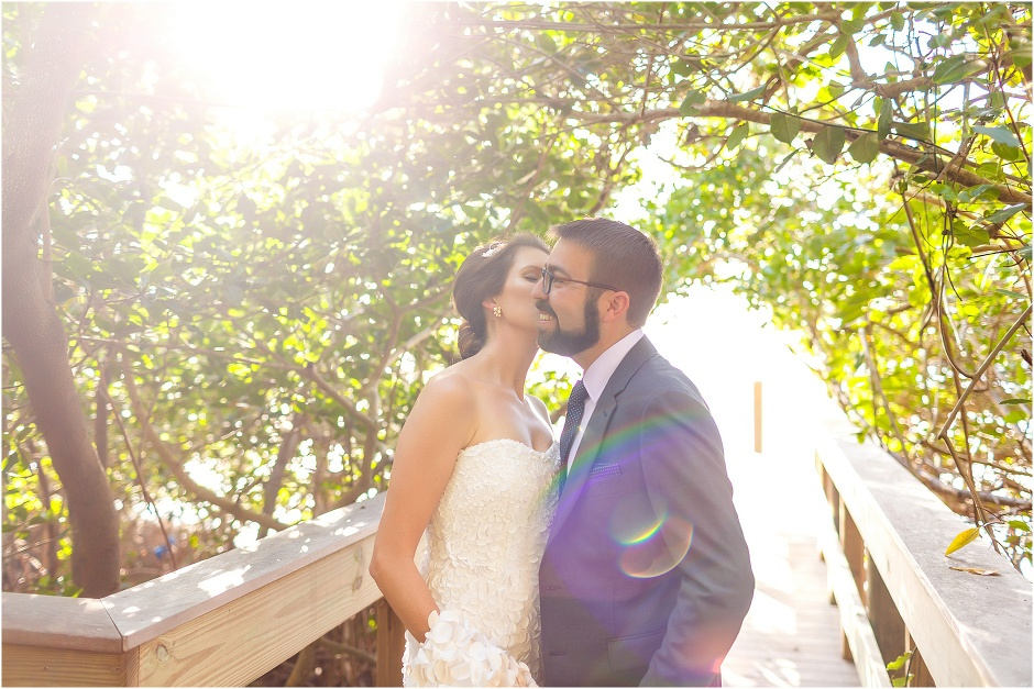 bride kisses groom as the sun rays burst through the banyon trees at Marie Selby Botanical Gardens