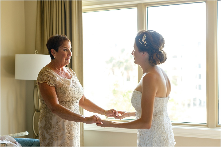 the bride and her mother hold hands as her mother takes her in